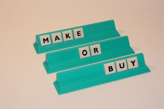 Buchstabenplatten bilden Make or Buy Analyse, das ist eine Vorgehensweise aus der BWL die bei der Entscheidung zu kaufen oder selbst herzustellen helfen soll